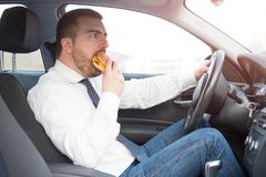 Man eating an hamburger and driving seated in car Royalty Free Stock Photo