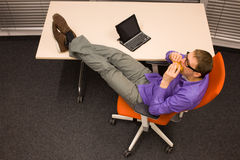 Man eating hamburger in office - fast food. Man sitting at with legs on the desk, heaving break in work eating hamburger in office royalty free stock photography
