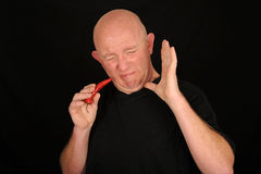 Man eating hot chili pepper Stock Photos