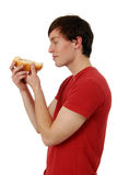 Man eating hot dog. Profile view of a man eating a hot dog in a bun Stock Photos