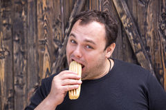 Man eating a hot dog. Brutal man eating a hot dog Stock Photos