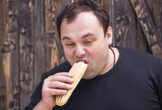 Man eating a hot dog. Brutal man eating a hot dog Royalty Free Stock Photos