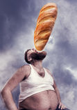 Man eating a huge bread. Fat man sits eating a huge bread over cloudy sky Stock Image
