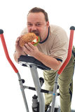 Man eating huge hamburger on a trainer device. Man eating huge hamburger while resting on a trainer device - isolated Royalty Free Stock Photography