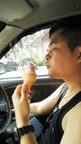 Man eating Ice cream. Asian singlet man enjoy with an icecream while driving Royalty Free Stock Photo