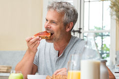 Man Eating A Jam Toast Stock Photo