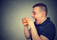Man eating junk food double cheeseburger. E profile of a man eating junk food double cheeseburger royalty free stock photos