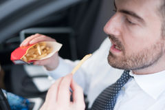 Man eating junk food and driving seated in car. Man eating junk food and driving seated in his car Royalty Free Stock Photos