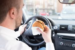 Man eating junk food and driving seated in car. Man eating junk food and driving seated in his car royalty free stock images