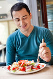 Man eating large portion of salad Royalty Free Stock Photos