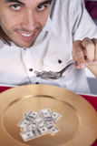 Man eating little dollar banknote Royalty Free Stock Image