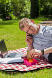 Man eating lunch in garden Stock Images