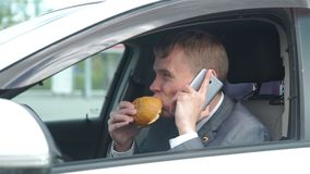 Man eating lunch and using mobile phone in car stock footage