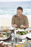 Man Eating Meal Near The Sea Stock Photo
