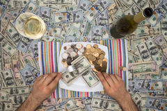Man eating money through extravagance. Conceptual image of a man eating money through extravagance with an overhead view of him sitting at a table covered in 100 Royalty Free Stock Image