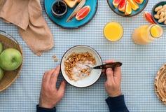 Man is eating muesli with yogurt, top view Royalty Free Stock Images