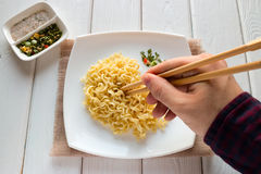 Man eating noodles with chopsticks Royalty Free Stock Image