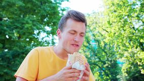 Man Eating Outdoors. A young man eating outdoors stock footage