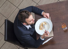 Man Eating Penne Pasta. Upper view of a young businessman eating Italian pasta in a restaurant Stock Photo