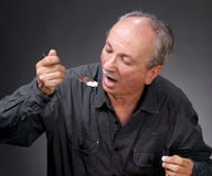 Man eating pills with a spoon Royalty Free Stock Images