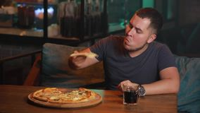 Man eating pizza in a bar stock video