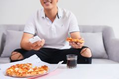 Man eating pizza having a takeaway at home relaxing resting royalty free stock photo