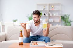 The man eating pizza having a takeaway at home relaxing resting Stock Photos
