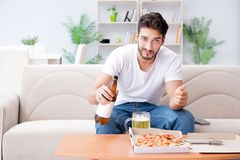 The man eating pizza having a takeaway at home relaxing resting Stock Image