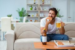 The man eating pizza having a takeaway at home relaxing resting Royalty Free Stock Photo