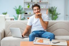 The man eating pizza having a takeaway at home relaxing resting. Man eating pizza having a takeaway at home relaxing resting stock photography
