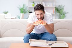 The man eating pizza having a takeaway at home relaxing resting Stock Images