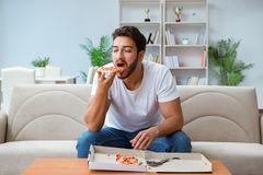 The man eating pizza having a takeaway at home relaxing resting Royalty Free Stock Photos