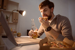 Man eating pizza and looking at computer Royalty Free Stock Photos