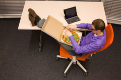 Man eating pizza in office. Man sitting at with legs on the desk,  eating pizza, in workplace Stock Photo