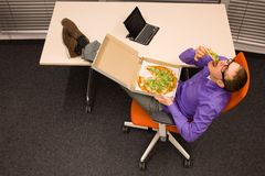 Man eating pizza in office. Man sitting at with legs on the desk,  eating pizza, in workplace Royalty Free Stock Photography