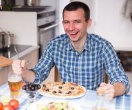 Man eating pizza and salad in the kitchen at home Royalty Free Stock Photos