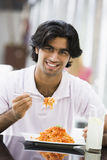 Man eating plate of pasta at cafe. Tables Stock Images