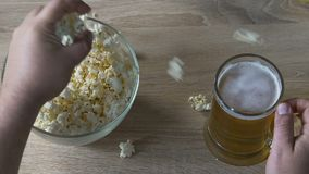 Man eating popcorn and drinking beer in the pub, relaxed weekend with friends. Stock footage stock video
