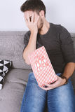 Man eating popcorn and watching movies. Stock Photo