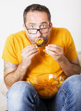 Man eating potato chips Royalty Free Stock Photos