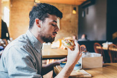 Man is eating in a restaurant and enjoying delicious food Royalty Free Stock Photography