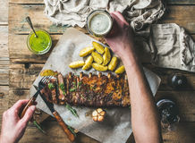 Man eating roasted pork ribs, holding fork and dark beer Royalty Free Stock Images