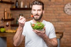 Man eating salad. Handsome bearded man in white t-shirt eating salad with tomatoes in the kitchen. Healthy and vegan food concept Royalty Free Stock Images