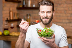 Man eating salad. Handsome bearded man in white t-shirt eating salad with tomatoes in the kitchen. Healthy and vegan food concept Royalty Free Stock Image