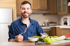 Man eating a salad at home Stock Images