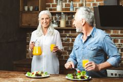 Man eating salad and looking at his wife stock photos