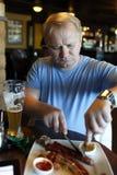 Man eating sausage Royalty Free Stock Photography