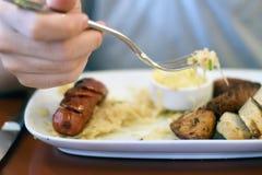 Man eating sausage, sauerkraut, and French mustard Stock Photography