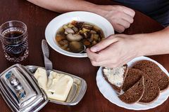 Man eating soup with his left hand. mushroom . bread. butter. Royalty Free Stock Photos
