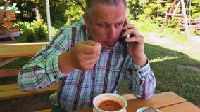 Man eating soup and talking on phone stock video